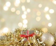 El regalo y las decoraciones de la Navidad se acurrucaron en guirnalda del oro foto de archivo
