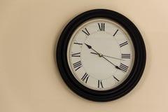 El reloj con los números romanos en el dial cuelga en la pared, cov fotos de archivo libres de regalías