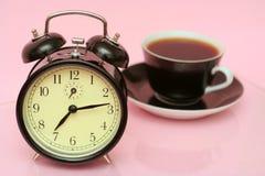 El reloj de alarma negro y la taza negra del café Foto de archivo