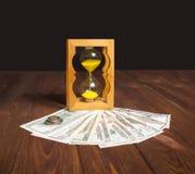 El reloj de arena antiguo brillante que se coloca con los billetes de dólar americanos fotos de archivo