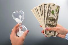 El reloj de arena de la señora y fan del dólar fotos de archivo