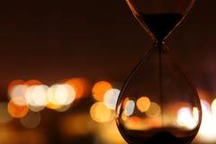 El reloj de arena sobre ciudad del bokeh se enciende como hora que pasa el concepto para el plazo del negocio Imagen de archivo libre de regalías