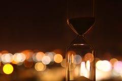 El reloj de arena sobre ciudad del bokeh se enciende como hora que pasa el concepto para el plazo del negocio Fotografía de archivo libre de regalías