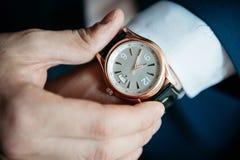 El reloj de los hombres en su primer de la mano Fotografía de archivo libre de regalías