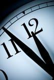 El reloj de pared análogo en una luz corta con las manos negras y los números con pocos minutos se fue a la hora de la media hora Imagen de archivo