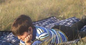 El reloj del niño pequeño al muchacho del smartphone es mentiras en la alfombra en la hierba en la tarde y agita sus piernas almacen de video