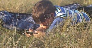 El reloj del niño pequeño al muchacho del smartphone es mentiras en la alfombra en la hierba en la tarde y agita sus piernas almacen de metraje de vídeo