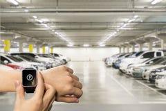 El reloj elegante a mano con recuerda parquear el coche app en la pantalla en un estacionamiento fotos de archivo libres de regalías