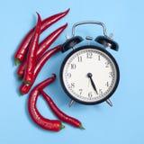El reloj en un marco de la pimienta de chile rojo - tarjeta para las recetas en fondo azul Fotografía de archivo libre de regalías