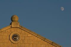 El reloj fijó en la construcción con el cielo azul y la luna Fotografía de archivo