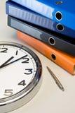 El reloj, la pluma y las carpetas Fotos de archivo