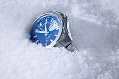 El reloj masculino en nieve. Imagenes de archivo