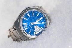 El reloj masculino en nieve. Foto de archivo
