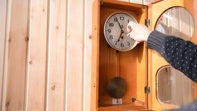 El reloj mecánico está colgando en la pared de madera metrajes