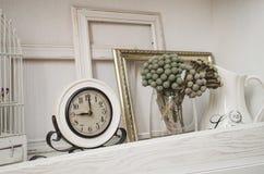 El reloj mecánico retro en estante y la decoración florece imagen de archivo