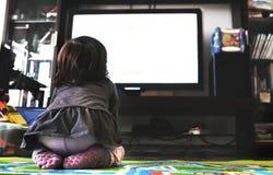 El reloj recién nacido TV del bebé en la alfombra en sala de estar pega la visión trasera imagen de archivo