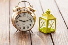 El reloj retro y adorna la lámpara en la tabla de madera Imagen de archivo libre de regalías