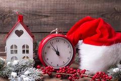 El reloj rojo del vintage, sombrero de Papá Noel, casa decorativa, ramifica piel Foto de archivo libre de regalías