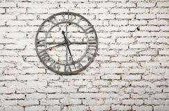 El reloj viejo del metal en blanco pintó la pared de ladrillo del grunge Imagen de archivo