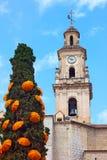 El reloj y la torre de Belces con los paraguas adornaron el árbol de ciprés Fotos de archivo libres de regalías