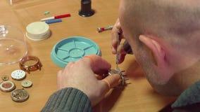 El relojero desmonta el reloj almacen de metraje de vídeo