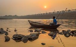 El remero se sienta en su barco para apuntalar en la puesta del sol en el río Damodar cerca de la presa de Durgapur Foto de archivo libre de regalías