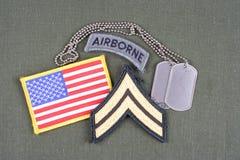 El remiendo espeso corporal del EJÉRCITO DE LOS EE. UU., la etiqueta aerotransportada, el remiendo de la bandera y la placa de id Foto de archivo