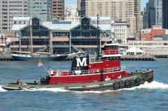 El remolcador rojo pasa el puerto del sur de la calle, Nueva York foto de archivo libre de regalías