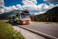 El remolque del camión transporta nuevos paseos de los coches en la carretera Foto de archivo libre de regalías