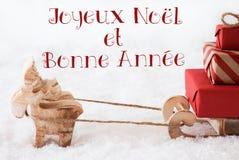El reno con el trineo en la nieve, Bonne Annee significa Año Nuevo Foto de archivo