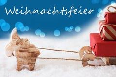 El reno con el trineo, fondo azul, Weihnachtsfeier significa a la fiesta de Navidad Fotografía de archivo