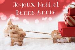 El reno con el trineo, fondo rojo, Bonne Annee significa Año Nuevo Imagen de archivo