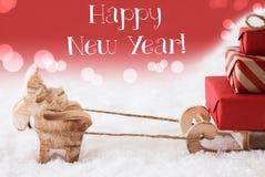El reno con el trineo, fondo rojo, manda un SMS a Feliz Año Nuevo Imagen de archivo