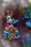 El reno de la Navidad en la Navidad viste sentarse en un trineo Fotos de archivo libres de regalías