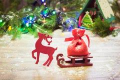 El reno de la Navidad lleva un trineo en un fondo de madera con las ramas y las guirnaldas spruce País de las maravillas del invi Foto de archivo