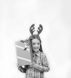 El reno del bebé feliz que lleva los cuernos con un regalo de la Navidad, es Foto de archivo