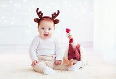 El reno lindo del bebé y su gallo compañero amontonan el juguete en fondo de la Navidad Foto de archivo