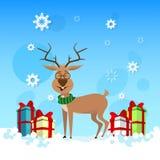 El reno sonriente de la Navidad con el presente del día de fiesta encajona la bandera de la celebración de la Feliz Año Nuevo Imagen de archivo