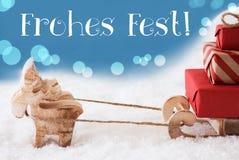 El reno, trineo, fondo azul claro, Fest de Frohes significa Feliz Navidad Imagen de archivo libre de regalías