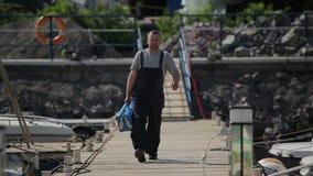 El reparador camina a lo largo del embarcadero almacen de metraje de vídeo
