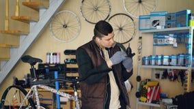 El reparador concentrado está engrasando el mecanismo mientras que repara la bicicleta en taller agradable Hombre joven en chalec metrajes
