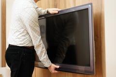 El reparador da la televisión abajo de la pared en sala de estar Fotografía de archivo