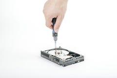 El reparador de la mano desatornilla la cubierta del motor de los 3 abiertos 5 pulgadas HDD con un destornillador Imágenes de archivo libres de regalías
