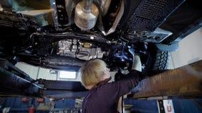 El reparador del taller del coche se está colocando bajo el automóvil levantado y detalles de examen, comprobando el contragolpe  almacen de metraje de vídeo