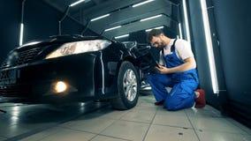 El reparador está examinando la rueda de coche con su ordenador portátil almacen de metraje de vídeo
