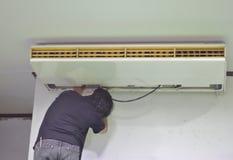 El reparador est? reparando el aire acondicionado en el techo Abra la cubierta del aire acondicionado detr?s del fondo blanco de  imágenes de archivo libres de regalías