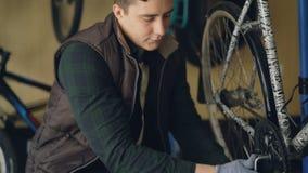 El reparador joven de la bicicleta está fijando el mecanismo del pedal de la bici usando llave especial Concentran al hombre en s almacen de video
