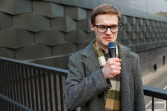El reportero profesional de las noticias en lentes con el micrófono está difundiendo en la calle Noticias de la moda o de negocio imagen de archivo libre de regalías