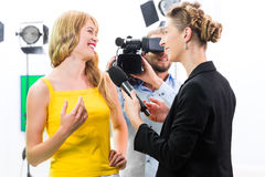 El reportero y el cameraman tiran una entrevista Imagen de archivo libre de regalías
