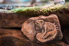 El reptil interesante representó en piedra el borde del bosque fotos de archivo